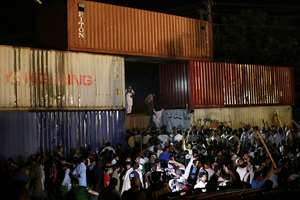 Imran Khan's supporters try to get past shipping containers placed by authorities to block their march to the Parliament in Islamabad.